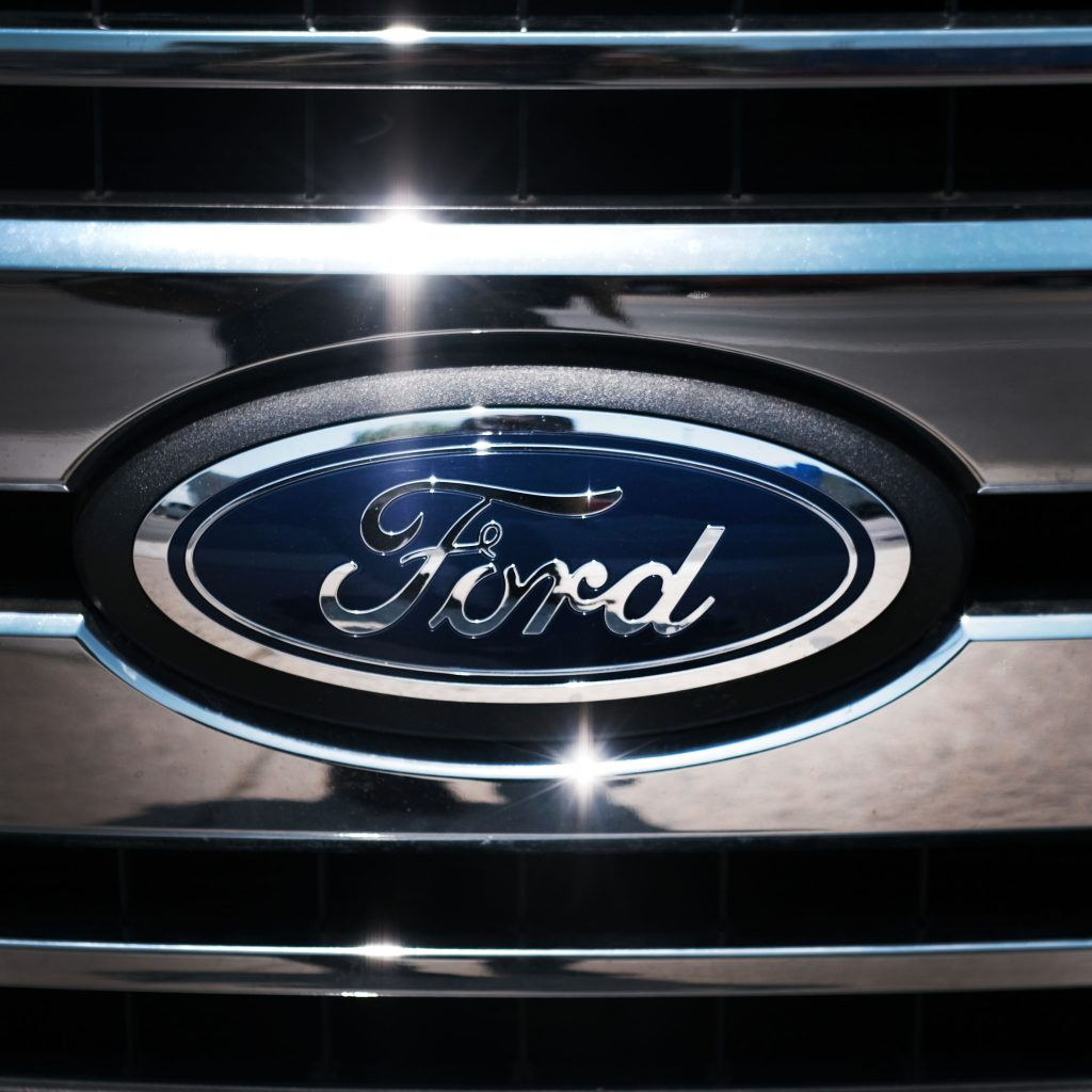 The blue Ford logo on a chrome grill of a car.