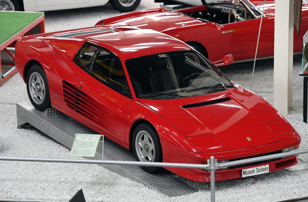 A red Ferrari Testarossa on display in a museum.