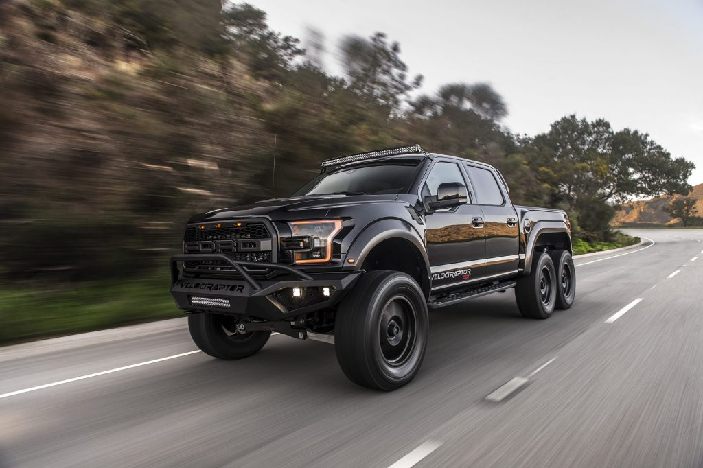 A black Hennessey Velociraptor 6x6 pickup on the road.