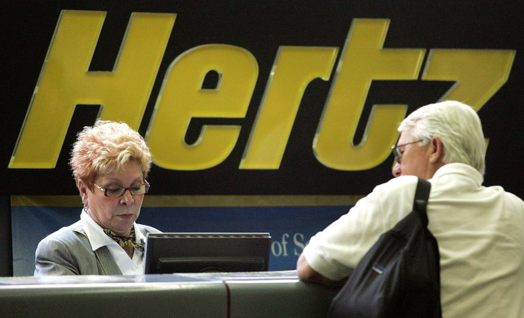 A customer is at the Hertz counter discussing a rental with an employee