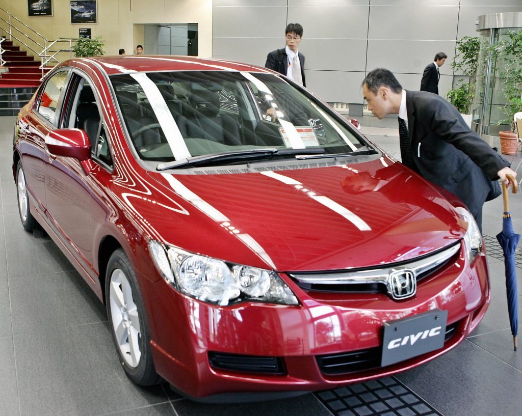 A car shopper inspecting a Honda Civic