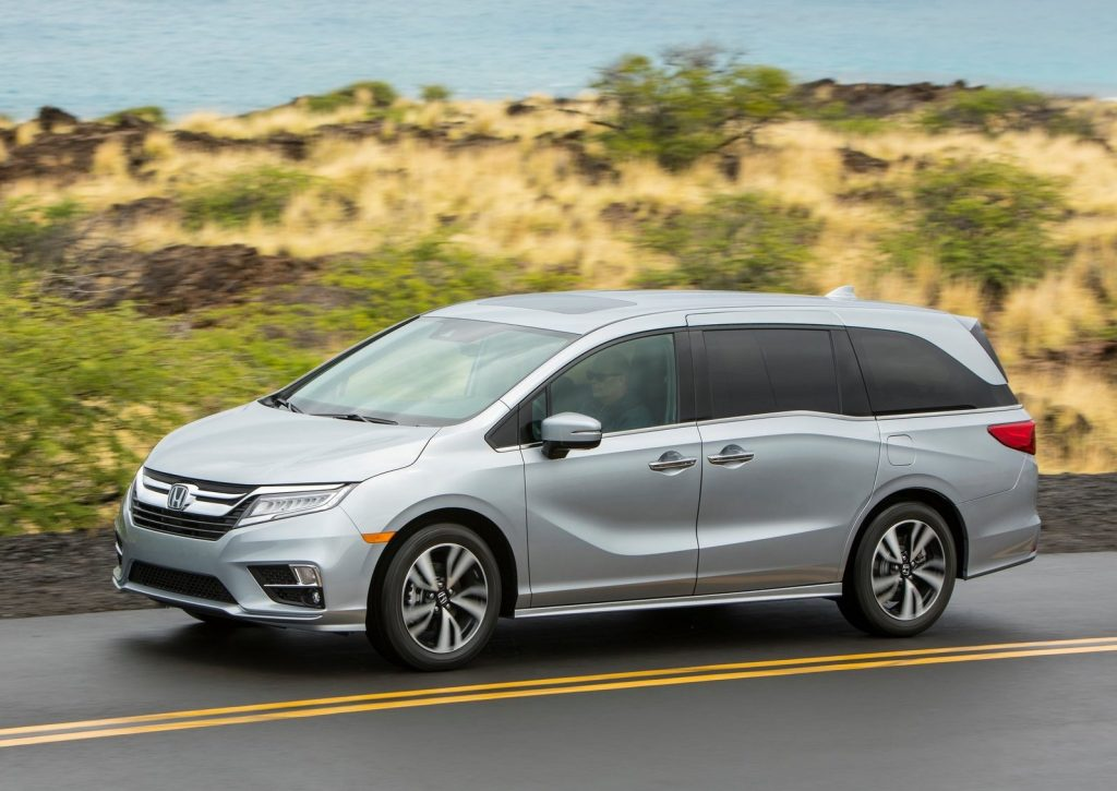 silver Honda Odyssey at speed on a scenic road