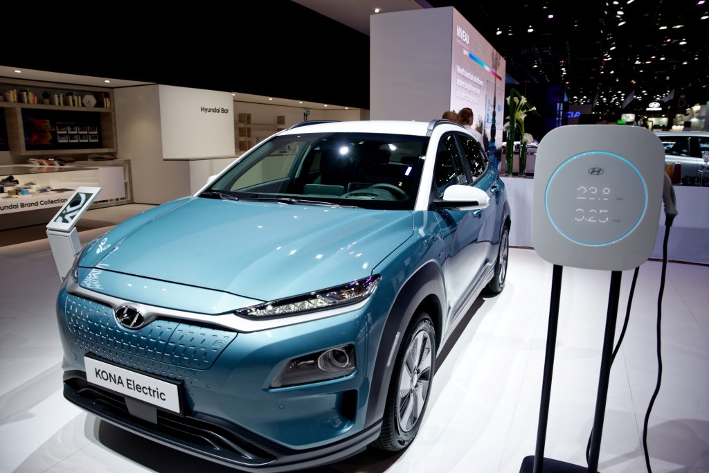 A blue Hyundai Kona Electric car sits on display next to a recharging unit.