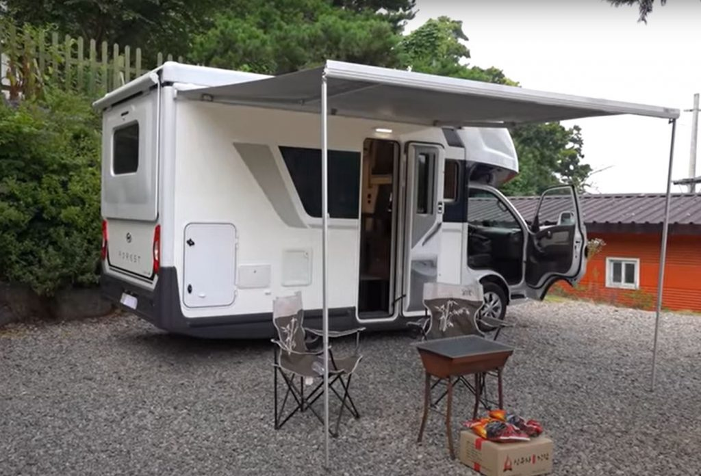 A campsite is set up under the canopy attached to a white Hyundai Porest RV.