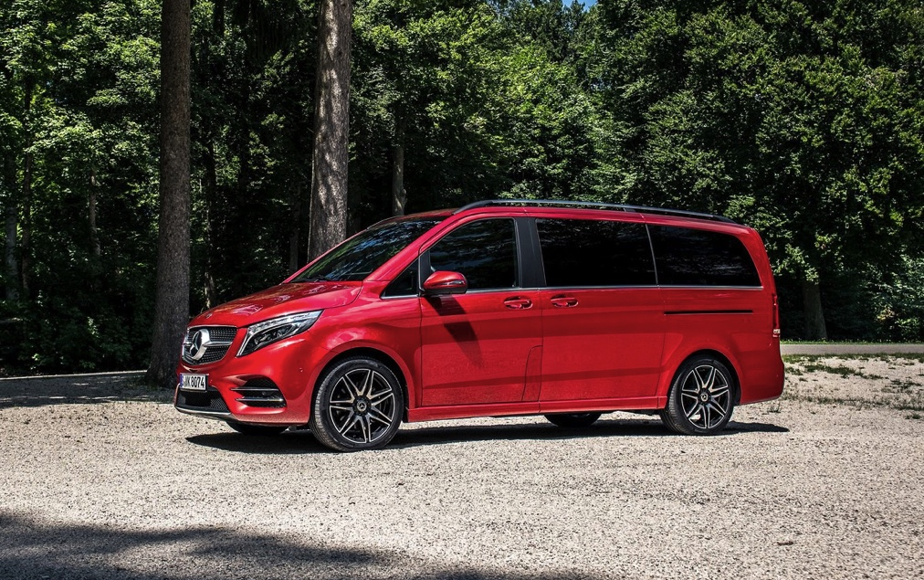 red mercedes minivan with a forested backdrop
