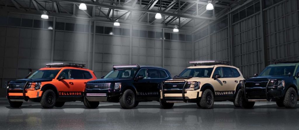 Four off-road ready modified Kia Telluride models are parked side by side.