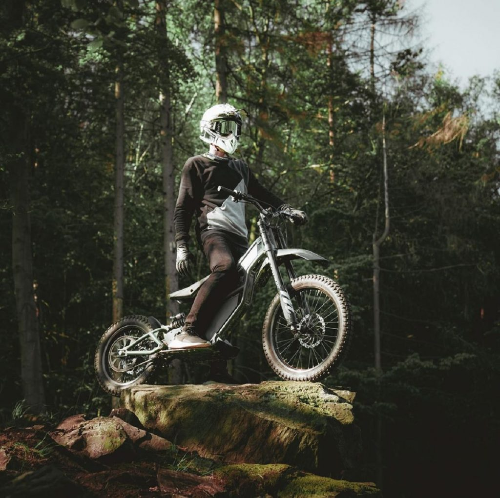 A white-helmeted rider on a green Kuberg Ranger, standing on a boulder in a forest