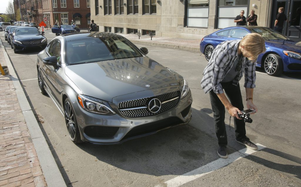 Greg Carloss [cq] of Baltimore shoots video of a Mercedes C300 coupe on Market Street