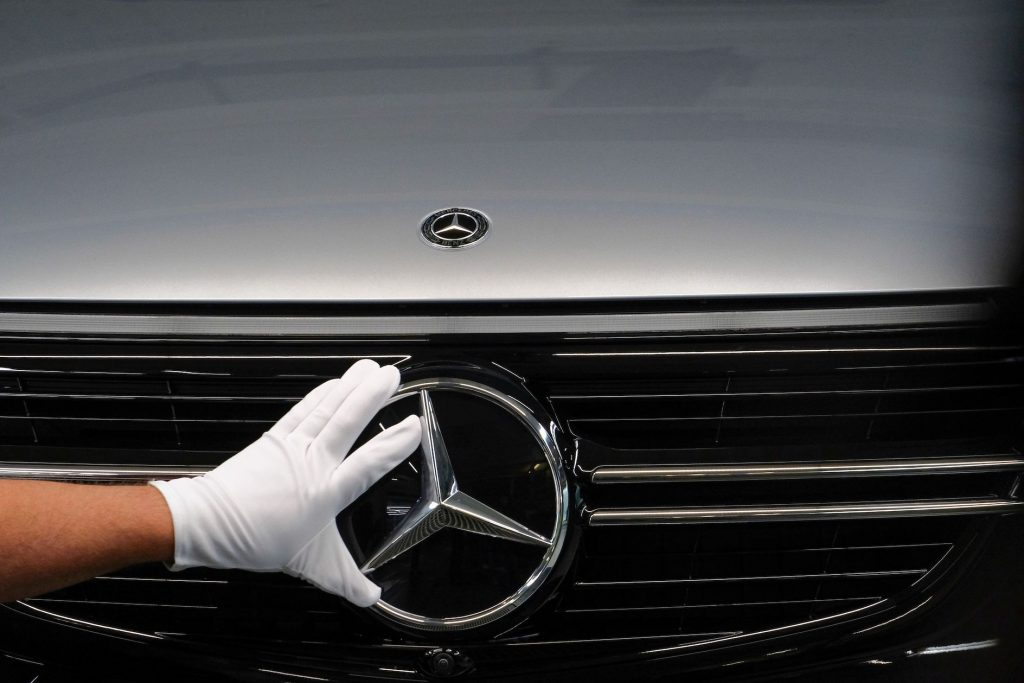 An employee adjusts a Mercedes-Benz three-pointed star emblem at an assembly line for GLC sports utility vehicle
