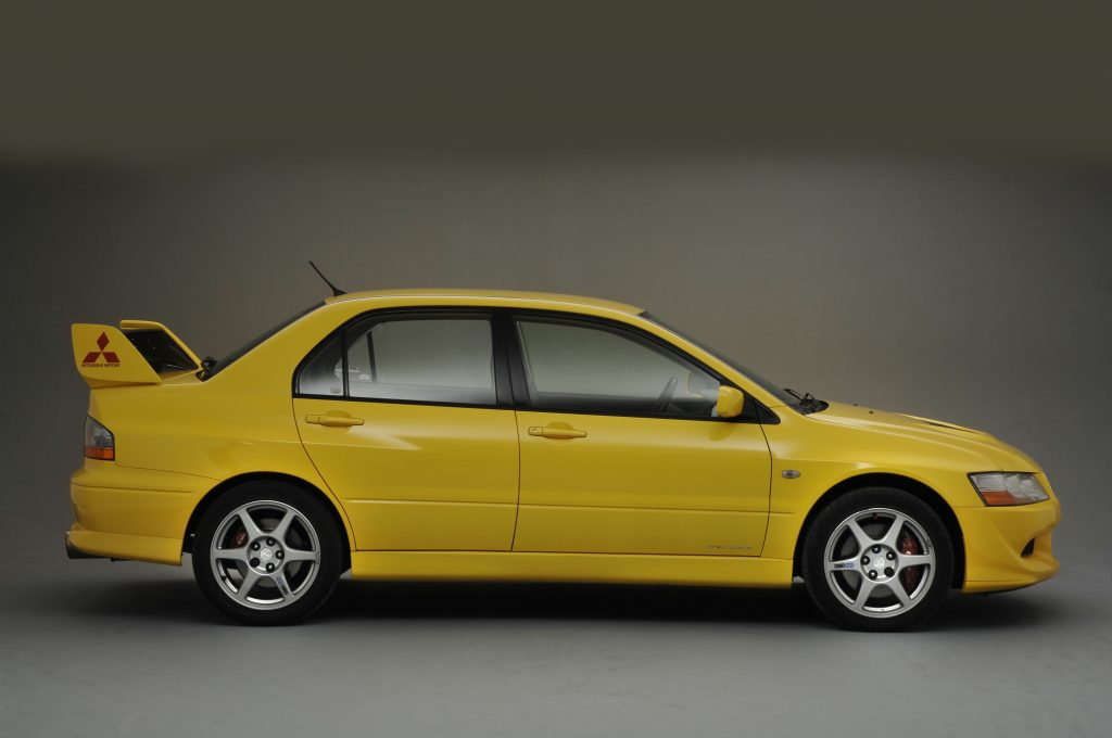 A yellow Mitsubishi Lancer with a spoiler
