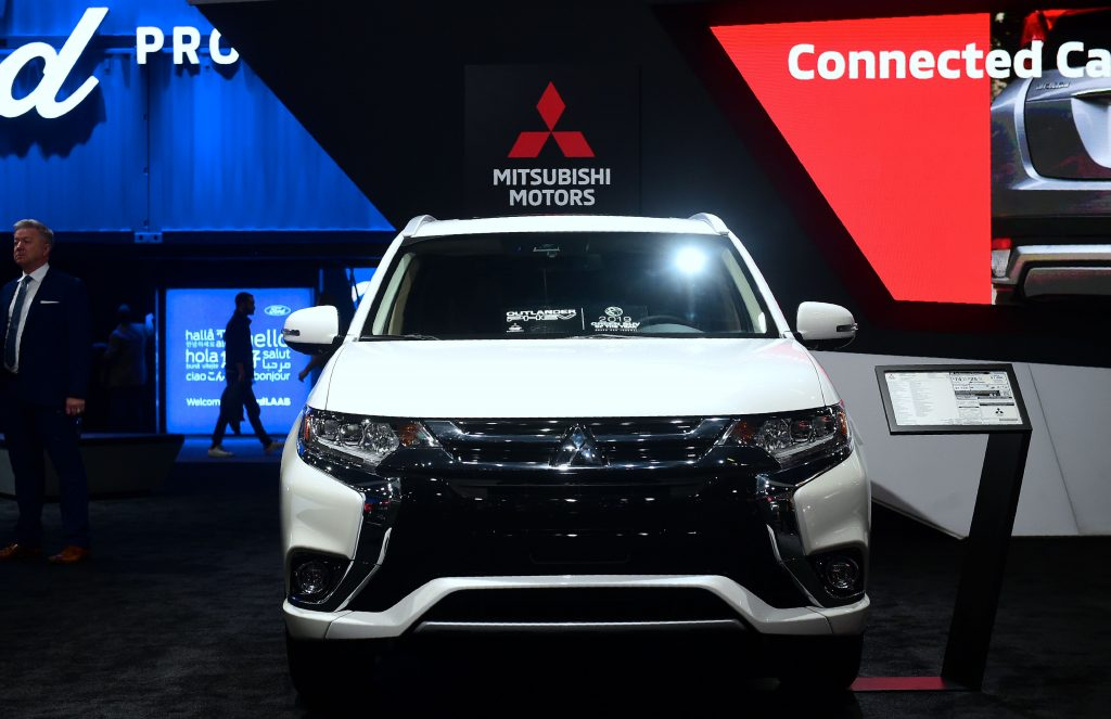 A white Mitsubishi Outlander on display at an auto show