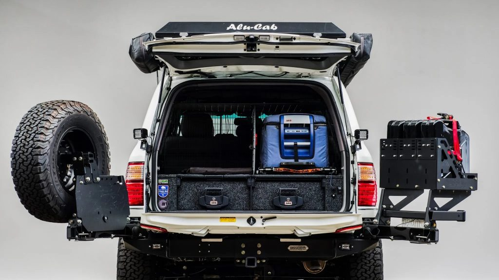 A rear view of a modified Modified 2005 Lexus LX470, showing the spare tire and numerous interior storage spaces