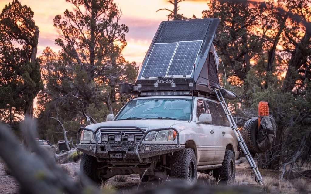 A modified 2005 Lexus LX470 in the wilderness with its rooftop tent open