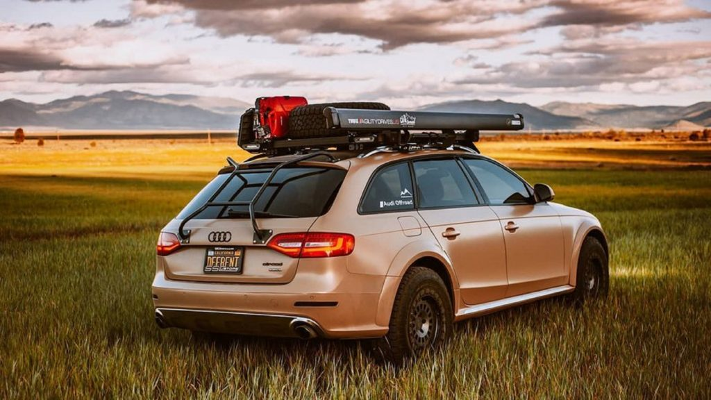 Rear view of a tan modified 2015 Audi A4 Allroad in an open sunset field