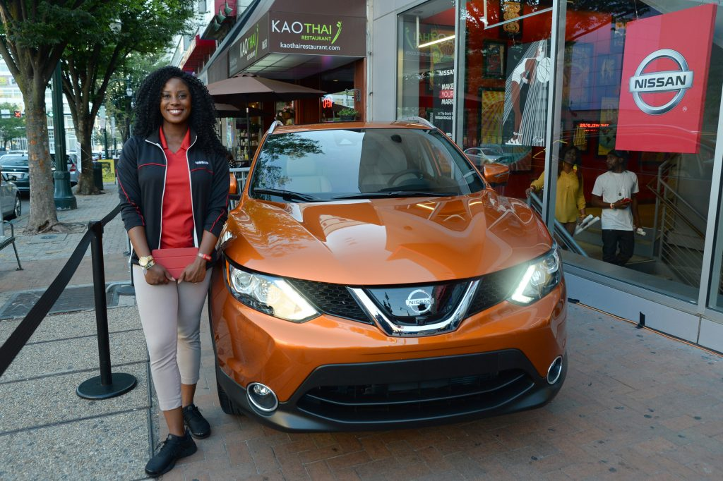 A woman standing next to a Nissan Rogue