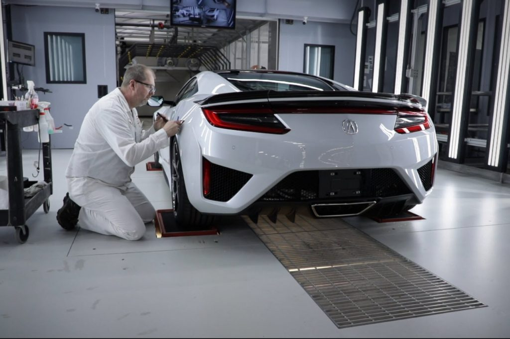 A paint tech inspects the paint of a white acura nsx
