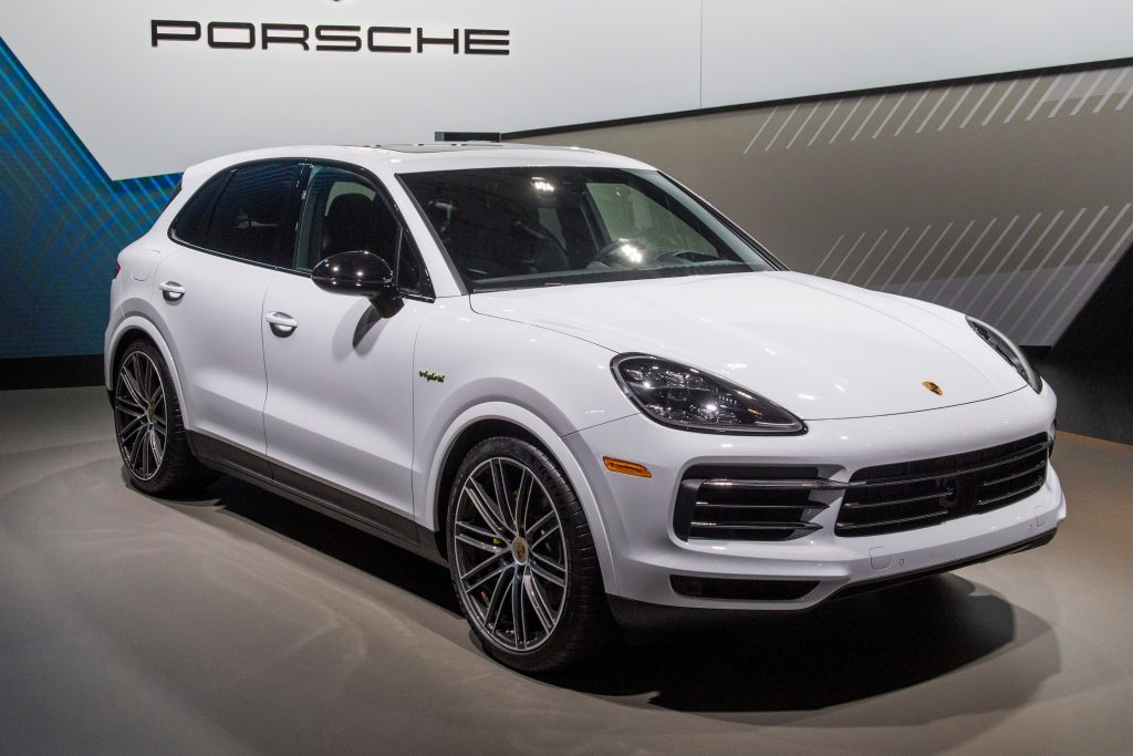 A white Porsche Cayenne Hybrid on display at an auto show
