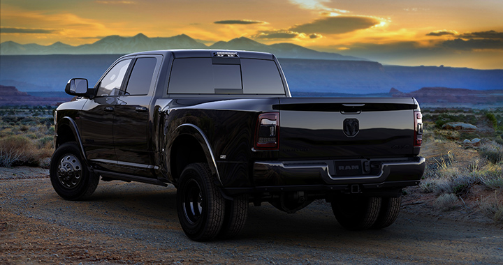 a black on black pickup truck by Ram trucks with a mountainous sunset backdrop