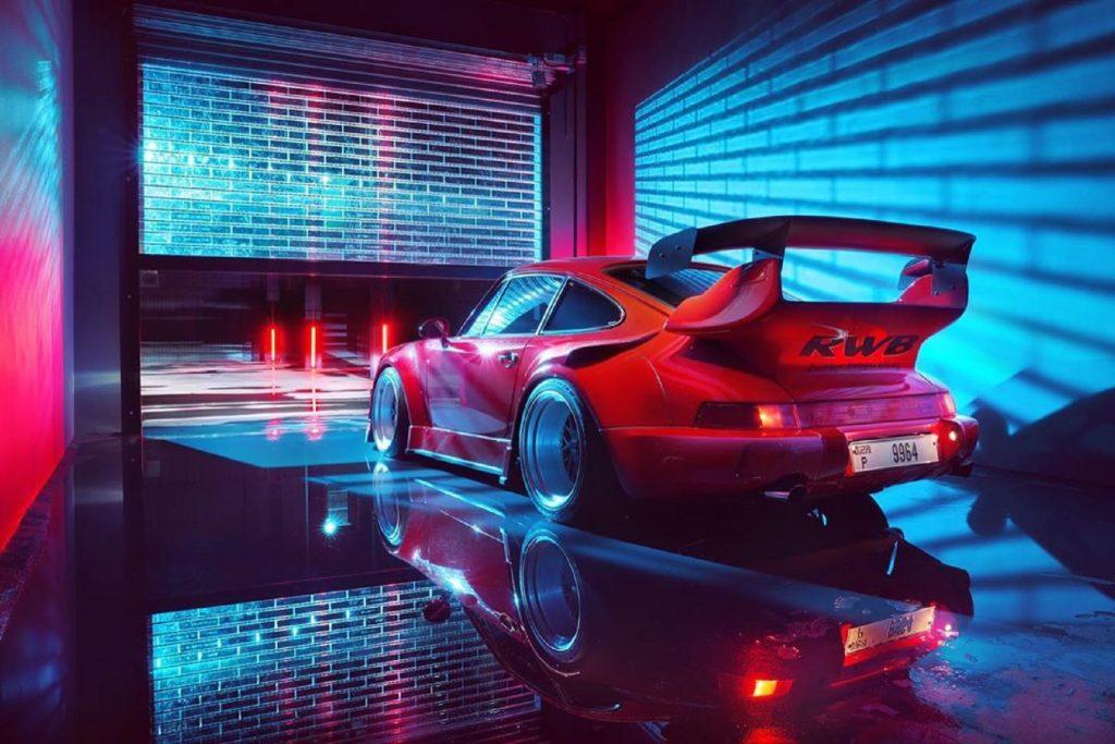 Rear view of a red RWB Porsche 911 as it sits in a neon-blue-lit garage