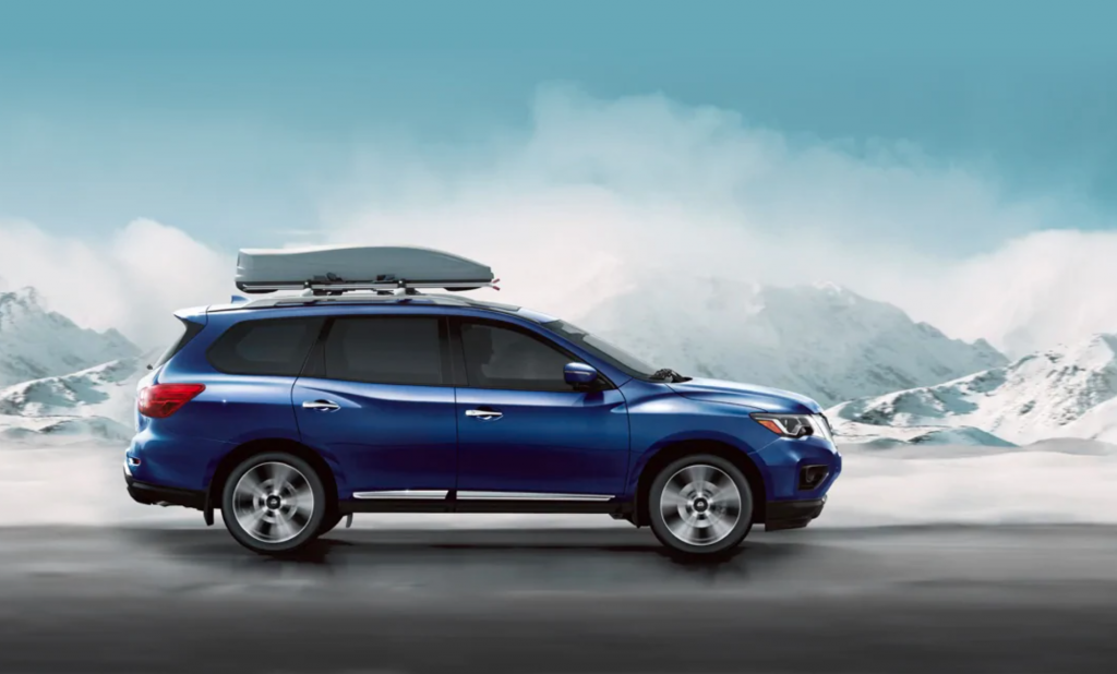A blue 2020 Nissan Pathfinder driving down snowy road