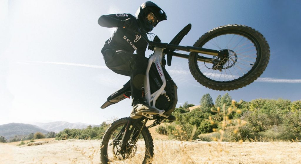 A rider does a wheelie while riding the white electric Segway eBike X260