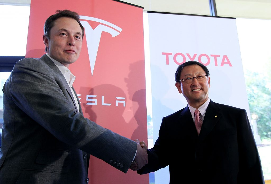 The CEOs of Tesla and Toyota shaking hands