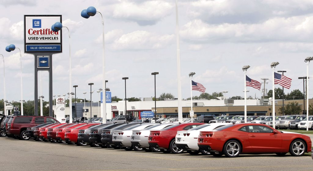 A line of cars at a used car dealership