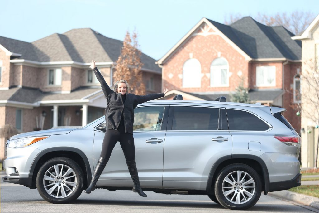 A woman posing in front of her Toyota Highlander