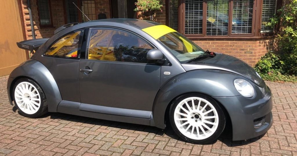 A gray Volkswagen Beetle RSI Cup Car with a yellow interior and roll cage