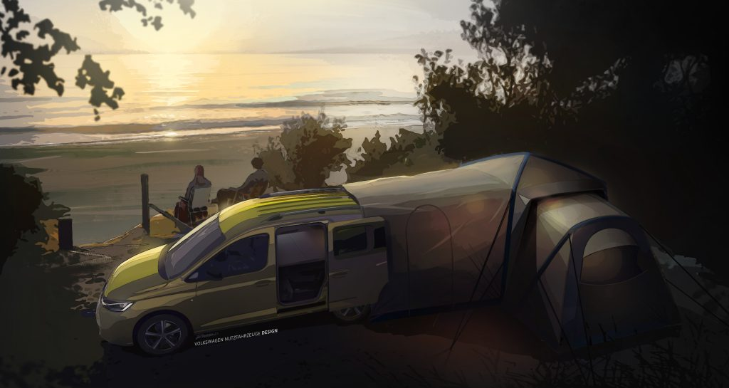 A green Volkswagen Caddy camper is set up on a hillside, with a tent attached to the back liftgate, at dusk.