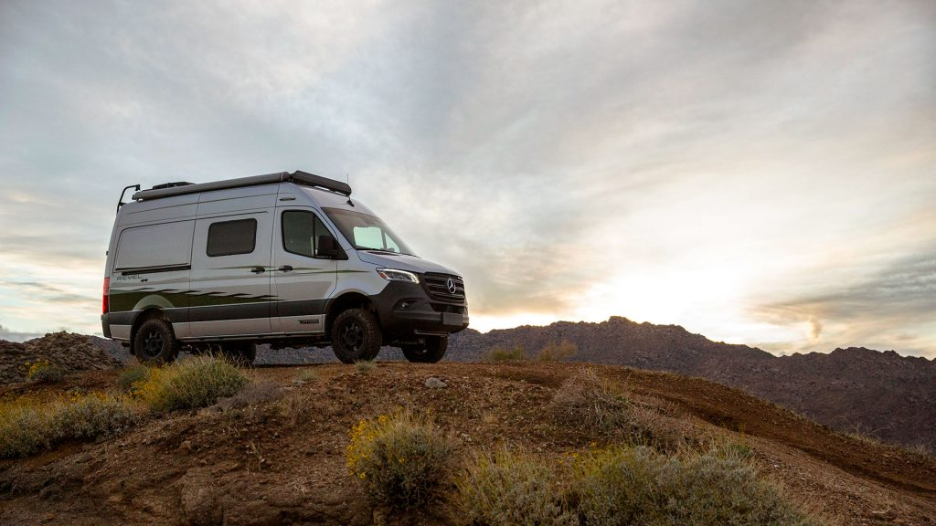 A silver Winnebago Revel RV sits atop a hill on at dusk.