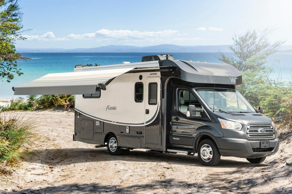 A black and white RV sits on a shore line with the awning deployed on a sunny day.