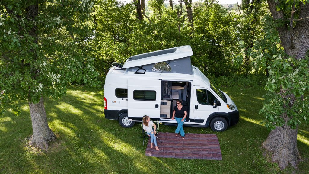 A drone takes a picture of a Winnebago Solis RV parked and set up at a campsite with two ladies sitting by it. The pop-top is extended on the roof of the RV.