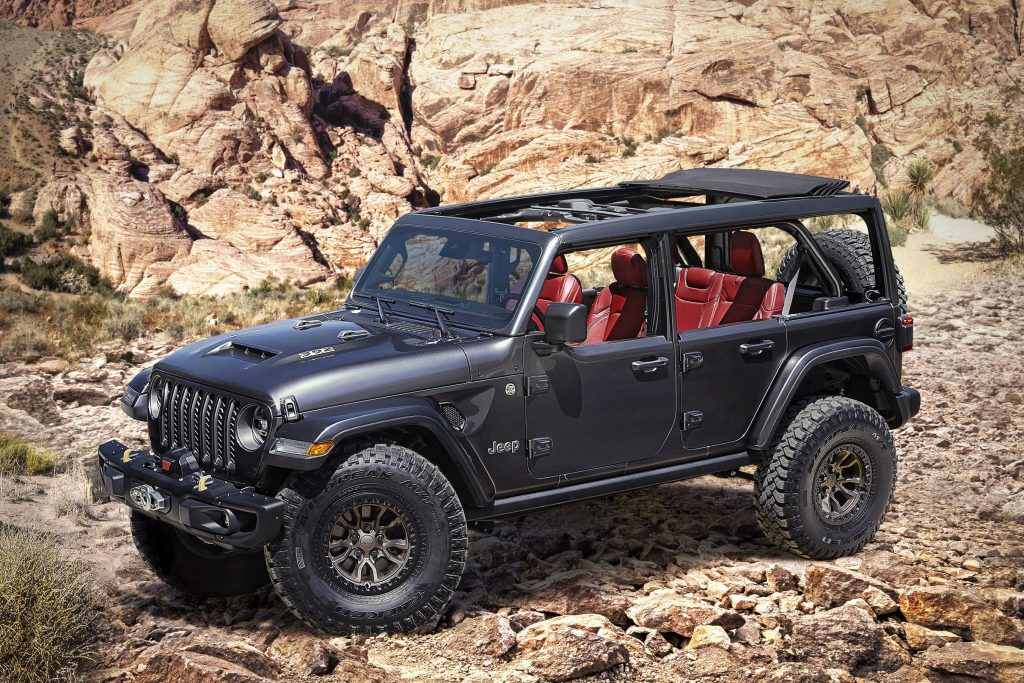 A black Jeep Wrangler with red interior sit at the base of rocky terrain with the tops off.