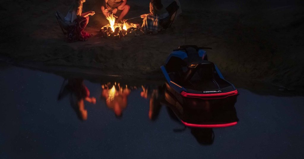 The rear lights of the Nikola Wav are on as it sits on shore by a campfire.
