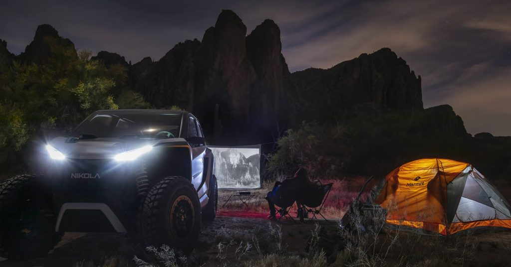 The electric NZT sits by a campsite with a makeshift screen in the background. The screen has a movie projected on it.