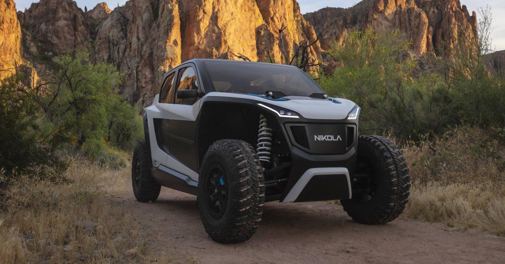 A white and black Nikola NZT ATV/UTV sits on a dirt canyon road.