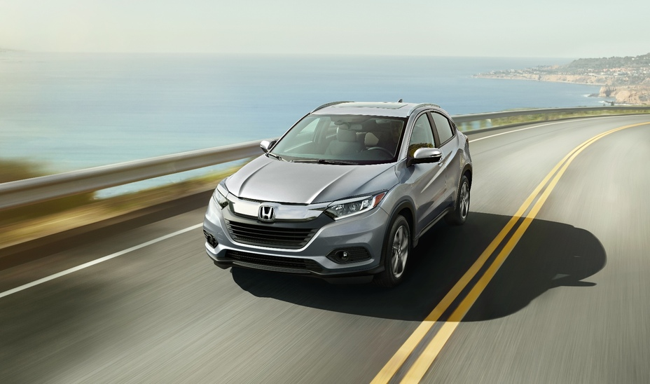 a silver top trim HR-V driving fast on a scene road by the shore