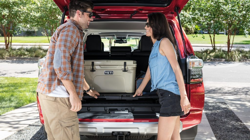 a couple loading a cooler in the wide cargo of a red 4runner