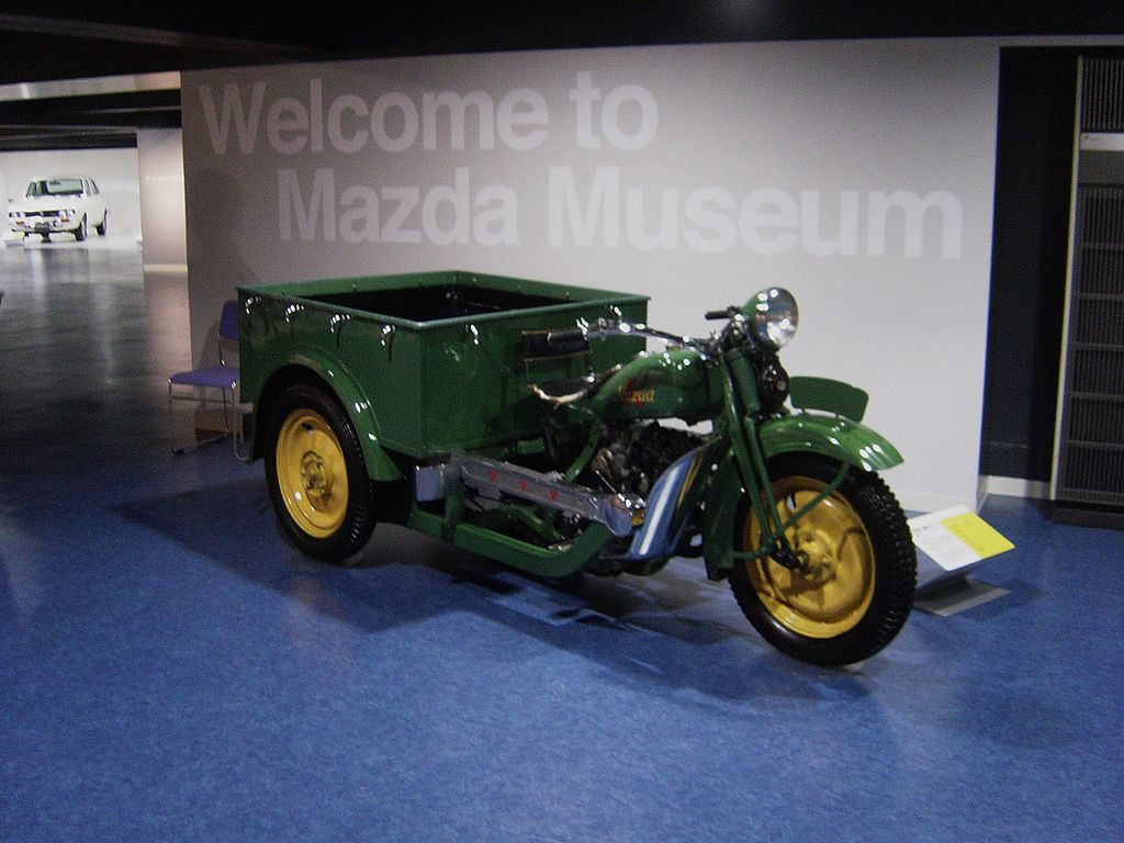a green and yellow Mazda-Go tricycle truck on display at a museum