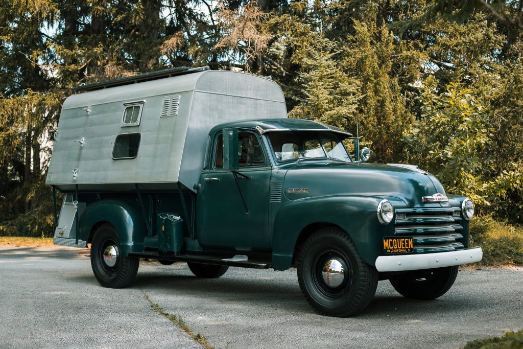 Parked on a driveway is Steve McQueen's Forest Green 1952 Chevrolet 3800 Dust Tite Camper