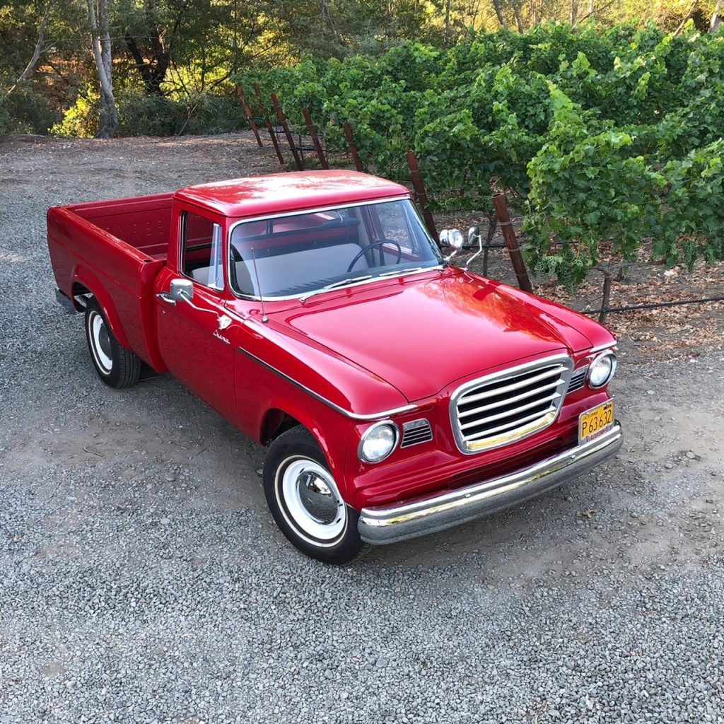 A red 1962 Studebaker Champ on a gravel driveway next to some bushes
