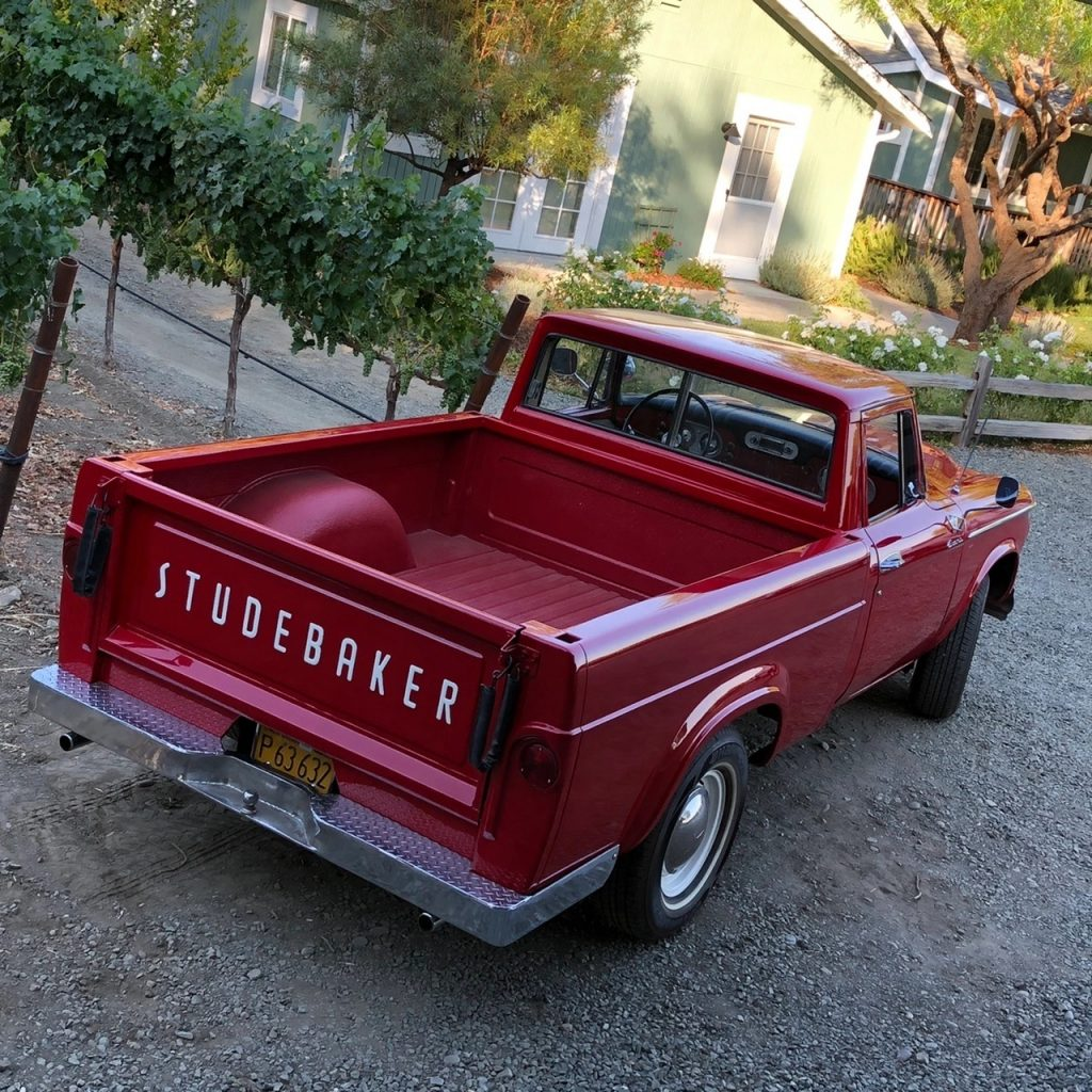 A rear overhead view of the red 1962 Studebaker Champ in front of a country home