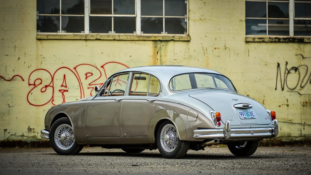 A rear-3/4 view of a two-tone gray 1964 Jaguar Mk2 in front of a yellow graffiti'd wall