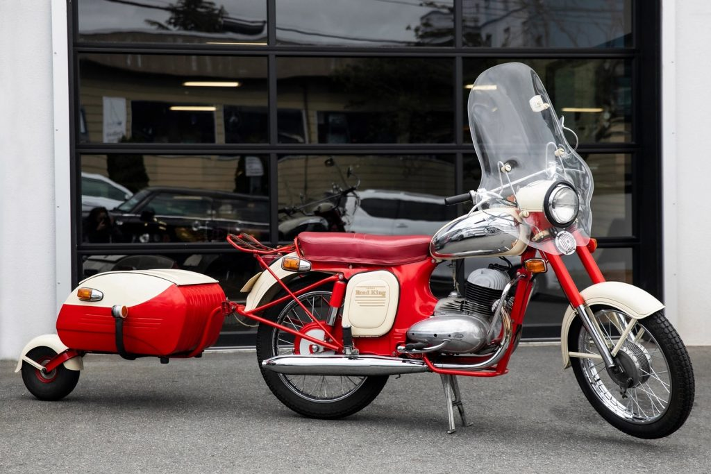 A red-and-white 1966 Jawa 350 with a one-wheel red-and-white trailer
