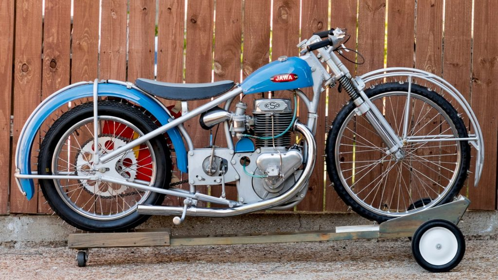 A blue 1967 Jawa/Eso factory ice racer motorcycle on a stand, with spiked ice tires in front of a wooden fence