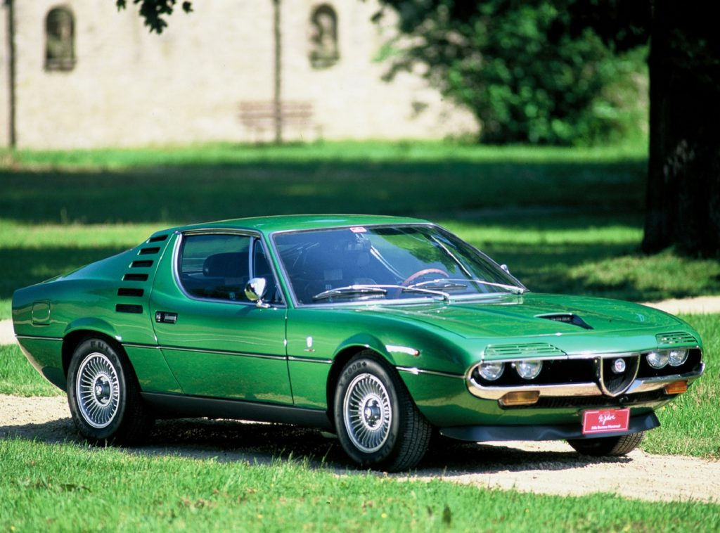 A green 1970 Alfa Romeo Montreal on a manicured estate lawn