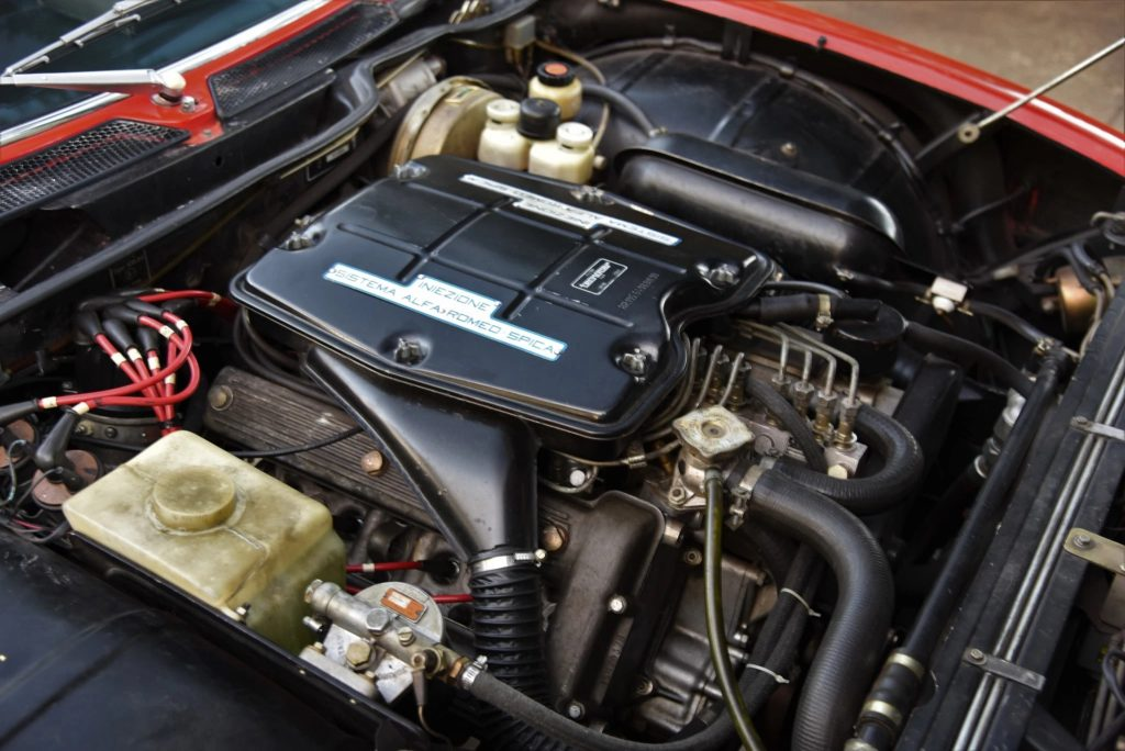 The 1972 Alfa Romeo Montreal's V8 engine with a label indicating its mechanical fuel injection