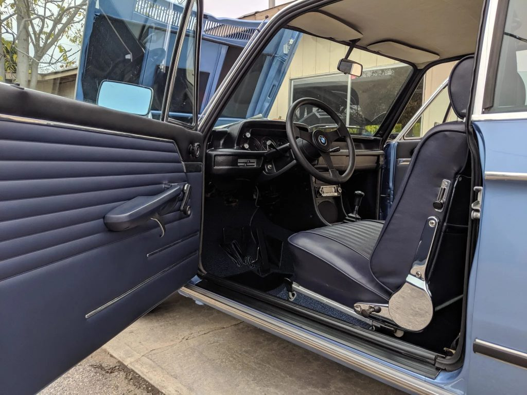 The interior of a blue 1972 BMW 2002tii, as seen through the open driver's door