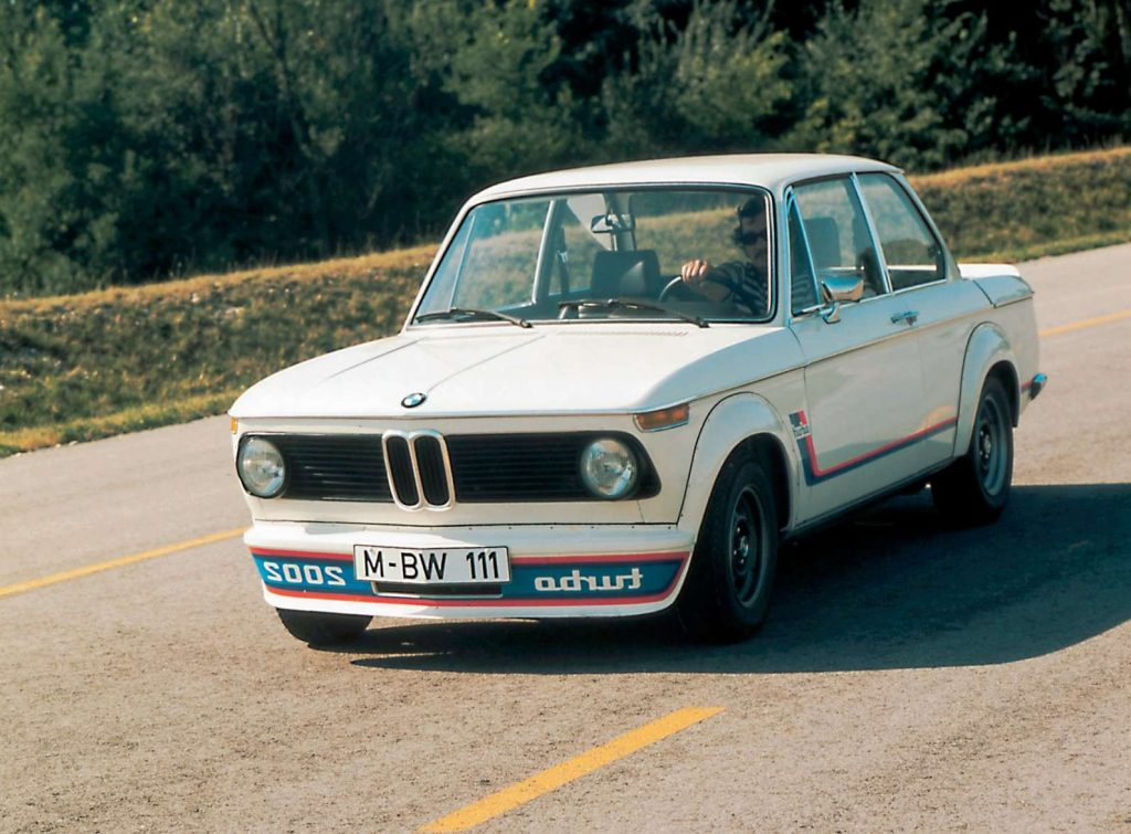 A white-with-red-and-blue-striping 1973 BMW 2002 Turbo drives down a sunny road